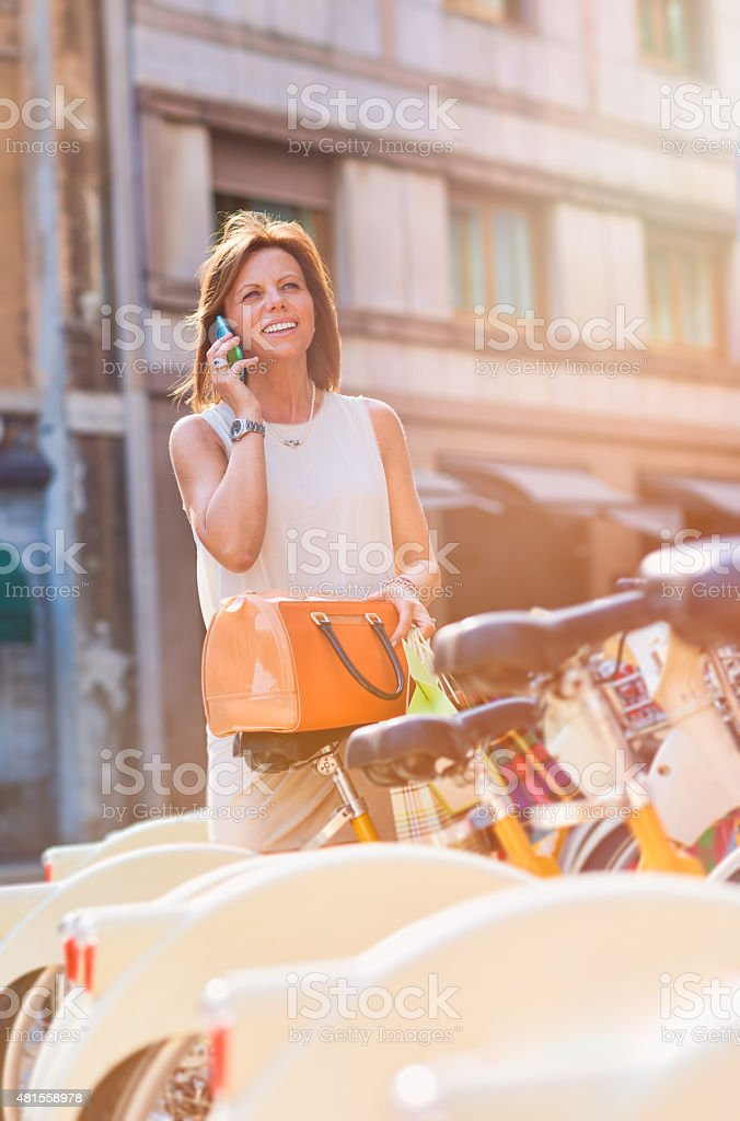 Real mature woman using smart phone on the street stock photo