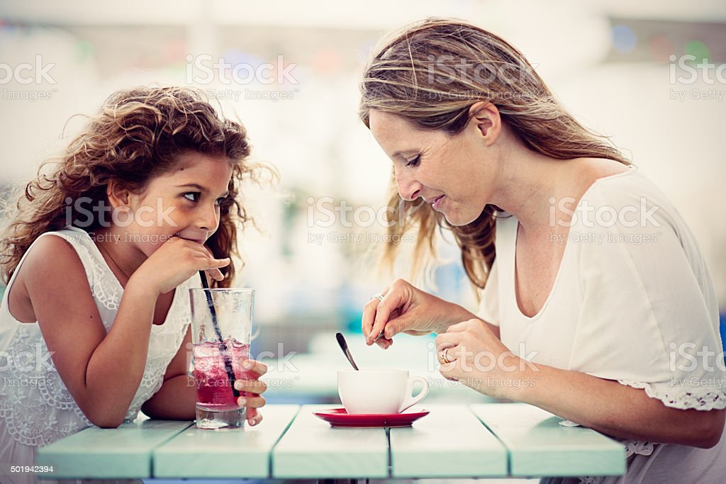 Real mother with daughter in sidewalk cafe stock photo