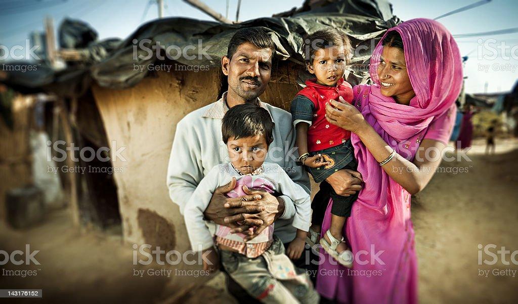 Happy parents with their children near their adobe house in slum...