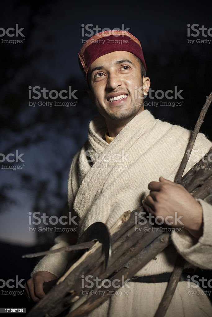 Real people from rural India: Man with wood and sickle royalty-free stock photo