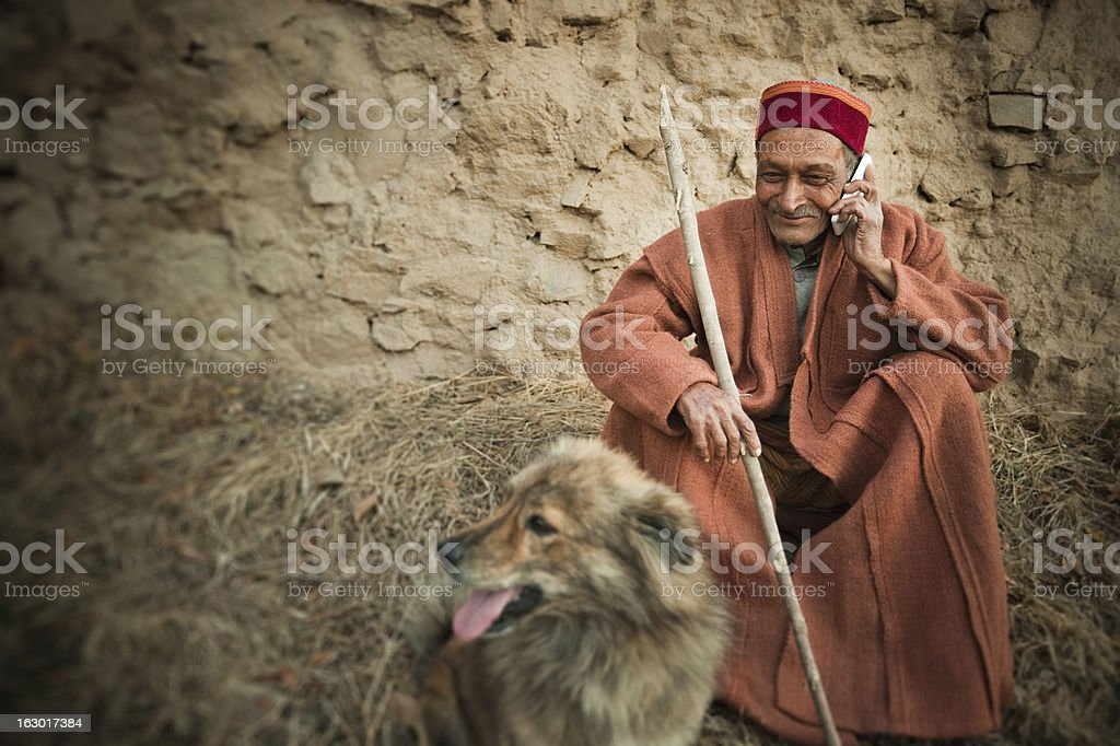 Real people from rural India: Senior Man using mobile phone stock photo