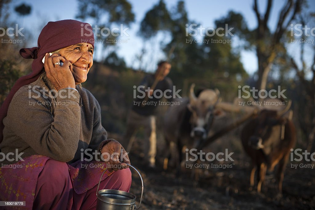 Real people from rural India: Senior peasant woman using phone stock photo