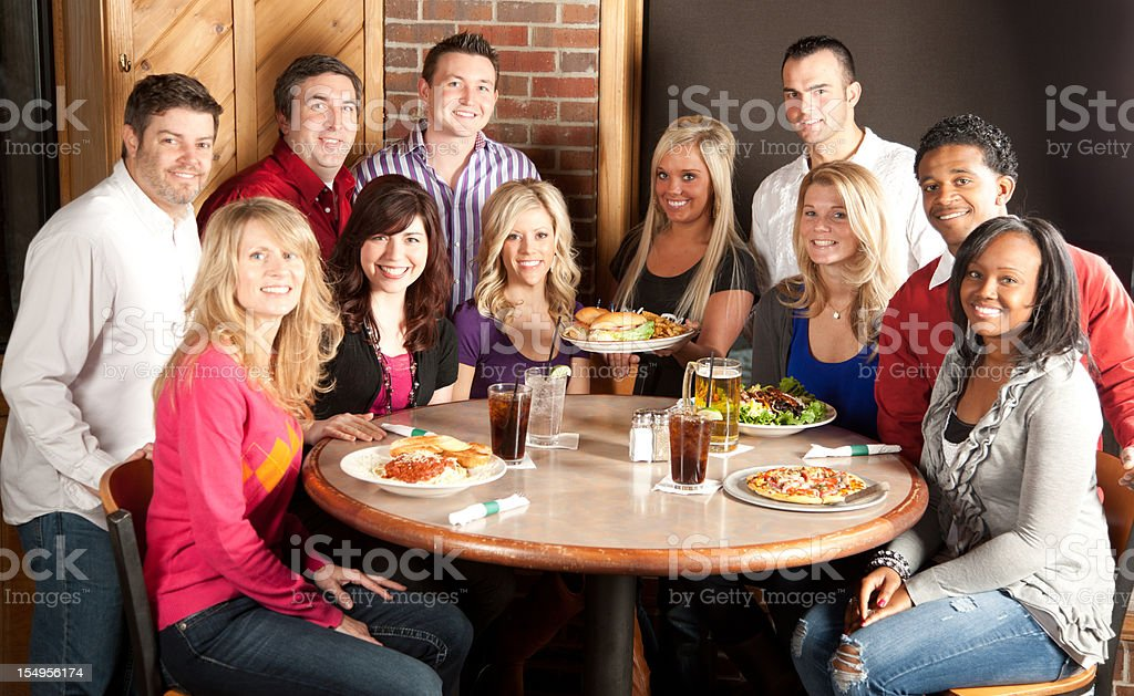 Real People: Group of Adults Eating Together at Restaurant royalty-free stock photo