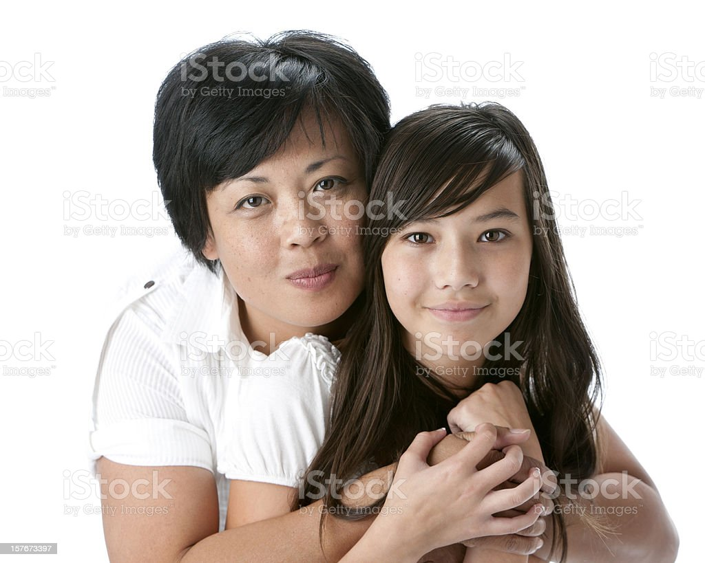 Real People: Head Shoulders Smiling Asian Mother Hugging Teenage Daughter stock photo