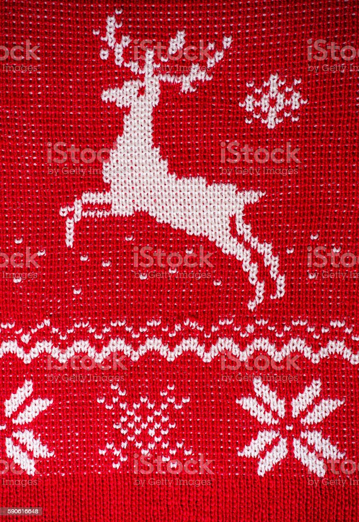 Real red knitted background with white Christmas reindeer stock photo