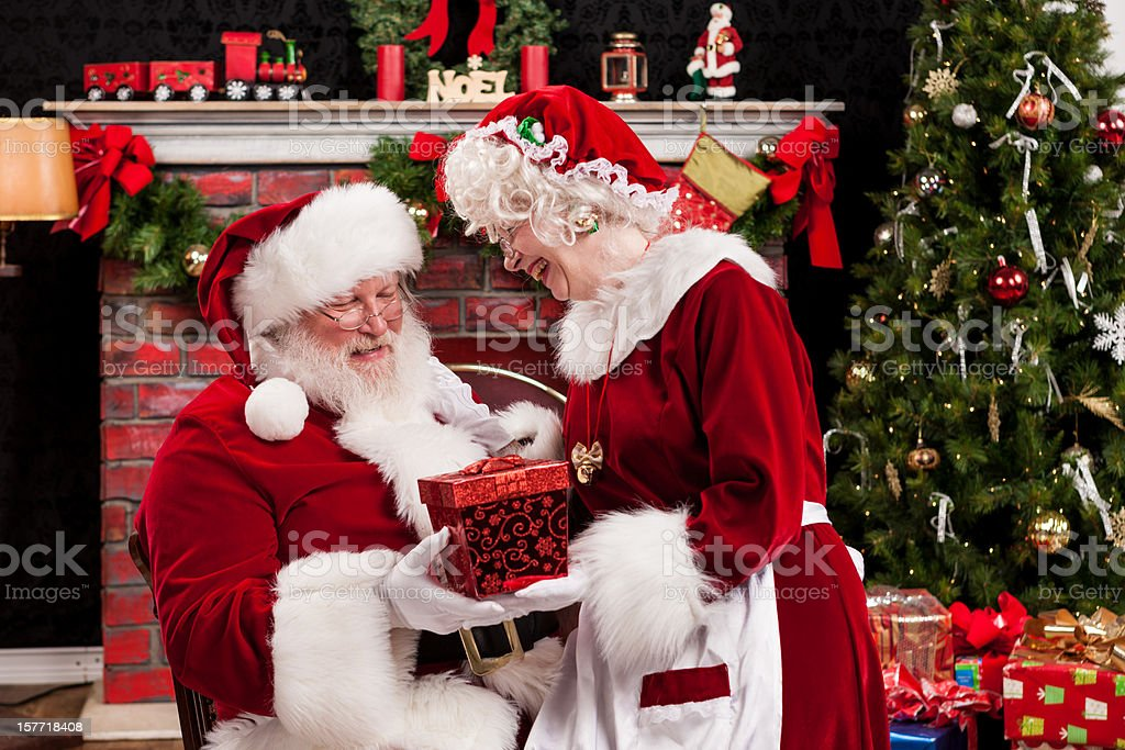 Real Santa and Mrs. Claus Giving Gifts to Each Other stock photo
