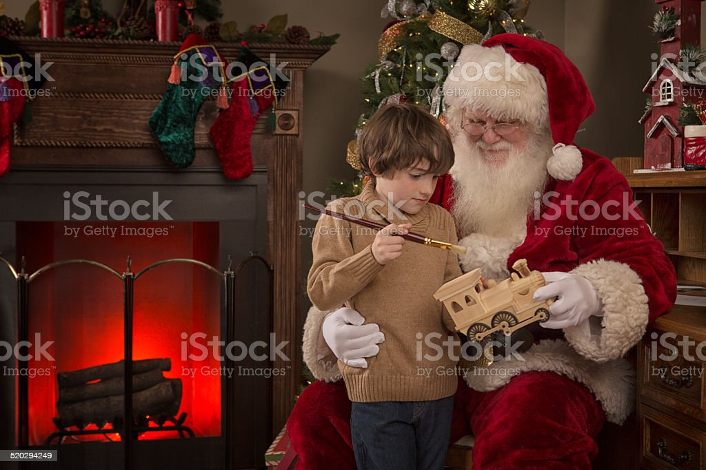 Real Santa Claus letting a boy paint a wooden train stock photo