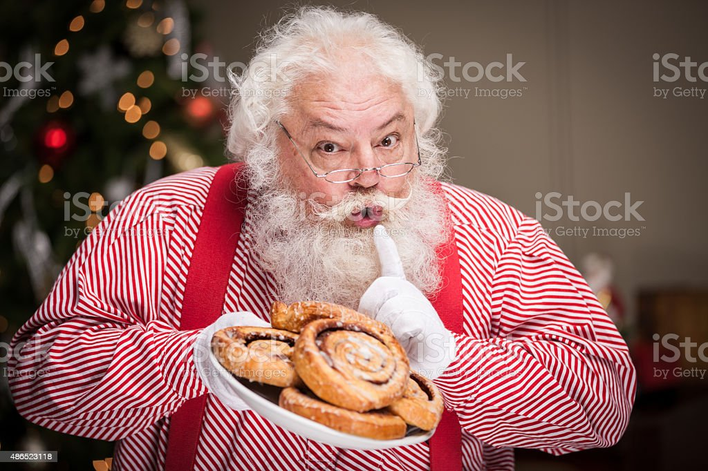 Real Santa Holding Plate of Cinnamon Rolls stock photo