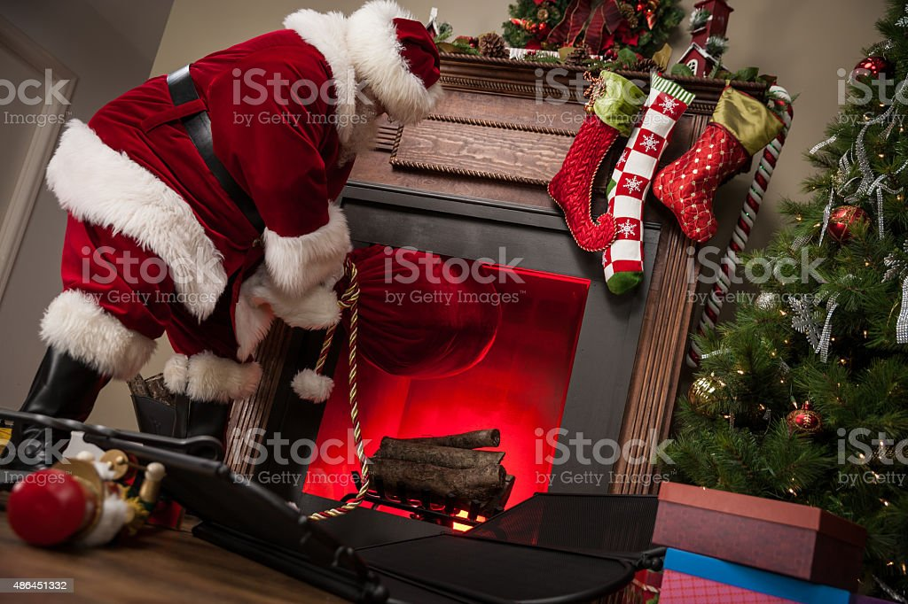 Real Santa Pulling Gift Bag Out Of Chimney stock photo