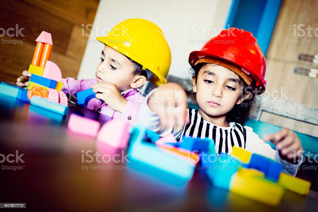 Real sister with brother playing in builders stock photo
