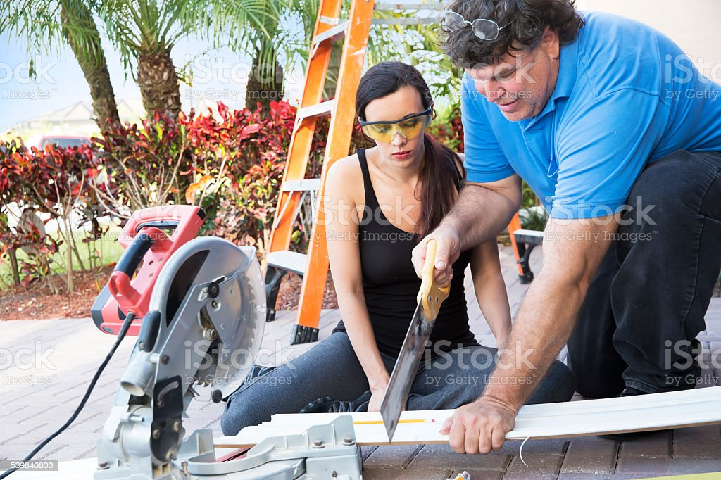 Real situation. Man is mentoring younger female construction worker stock photo
