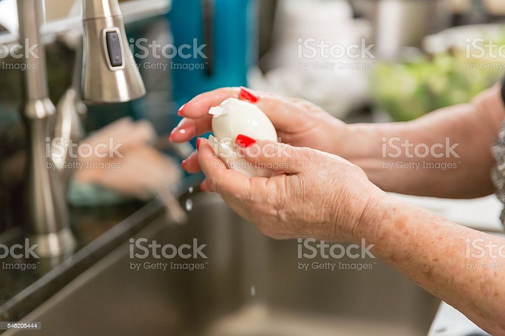 Real situation- Senior woman peeling hard boiled egg in kitchen stock photo