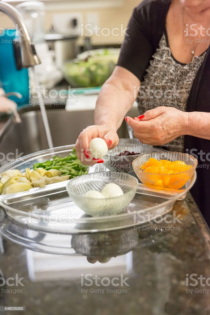 Real situation Senior woman putting hard boiled egg on tray. stock photo