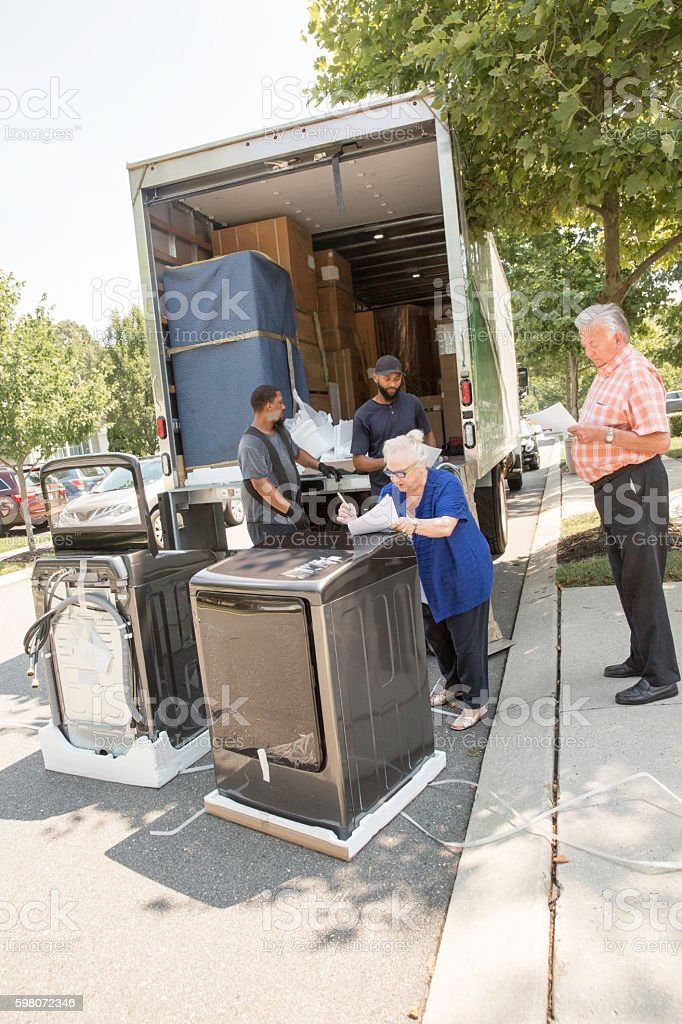 Real Situation-Senior couple receives delivery of new appliances stock photo
