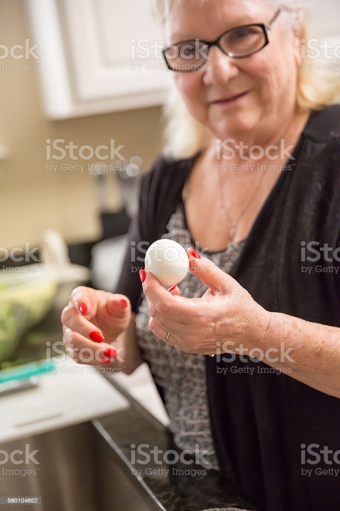 Real situation-Senior woman holding a hard boiled egg in kitchen stock photo