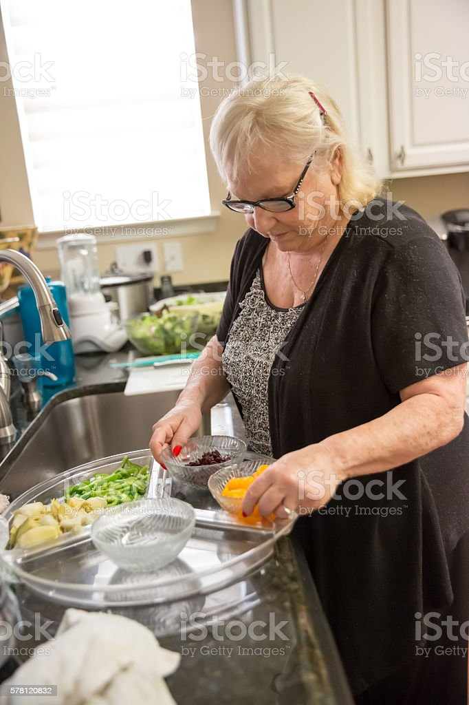Real situation-Senior woman preparing a platter of fruits and vegetables stock photo