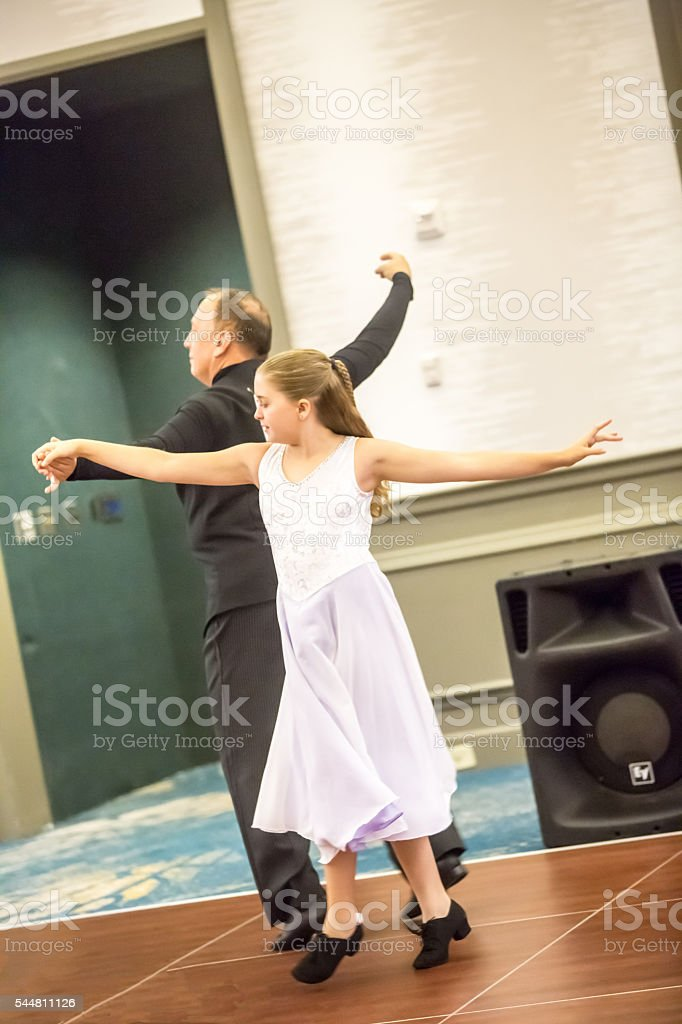 Real tween girl competes in junior ballroom dance competition stock photo