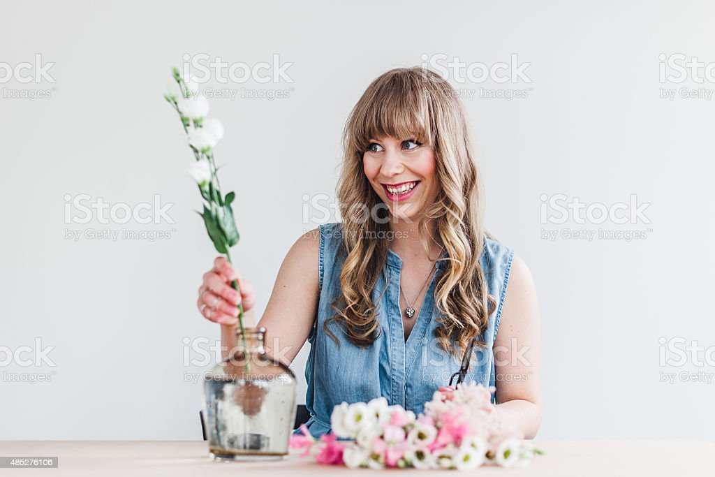 real woman decorating with flowers at home royalty free stock photo
