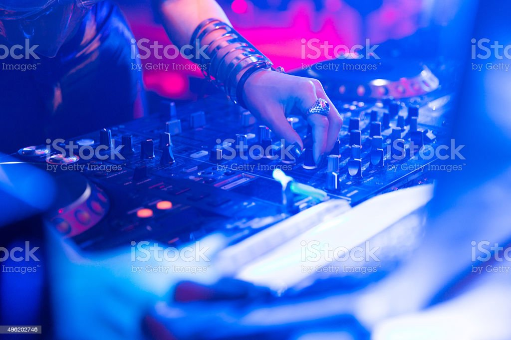 real woman dj playing music at party stock photo