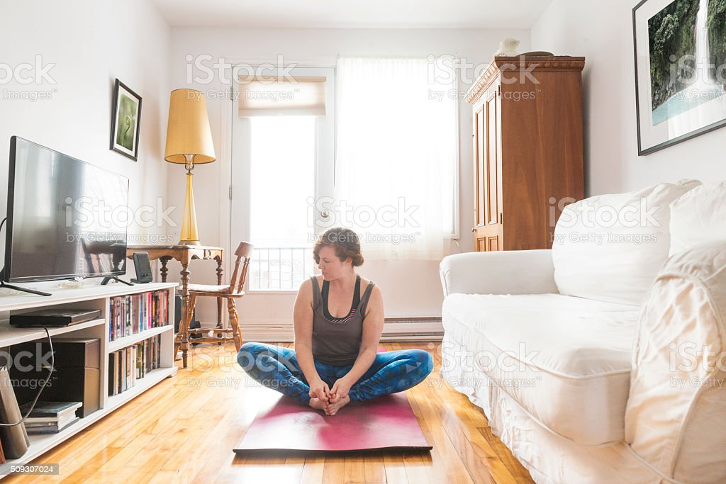 Real Woman Doing Yoga Exercise in Home Living Room stock photo