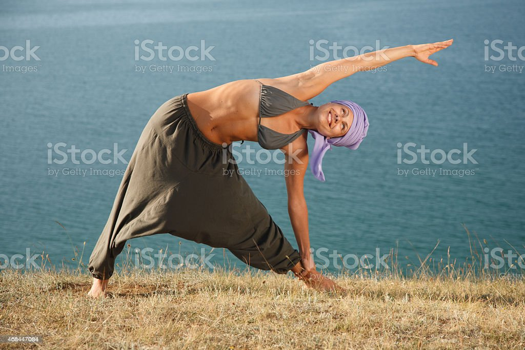 Real yoga instructor practicing on the rock near water line stock photo