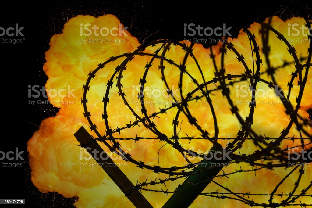 Realistic orange fire explosion behind restricted area barbed wire fence stock photo