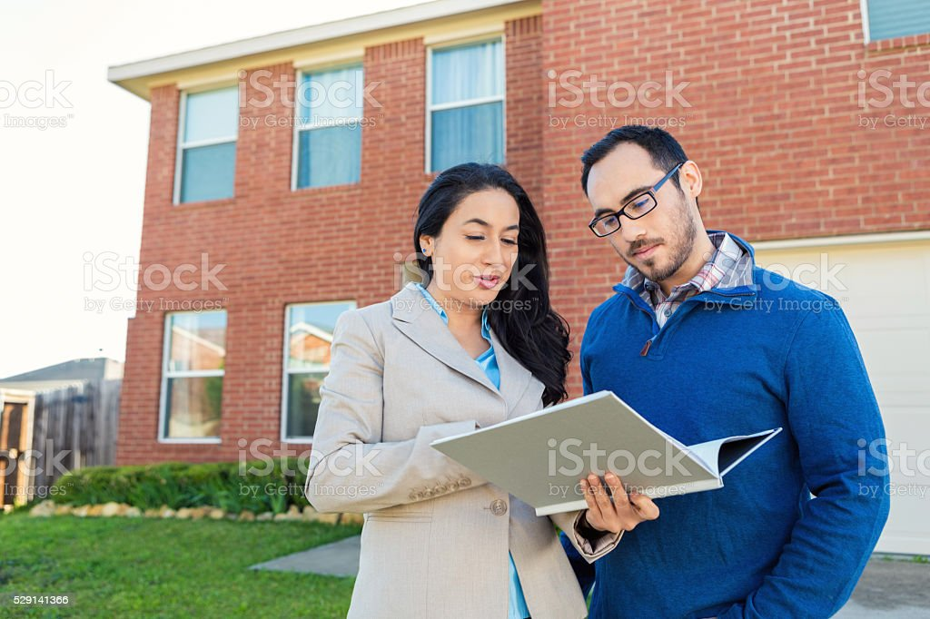 Realtor discusses paperwork with client in front of new home stock photo