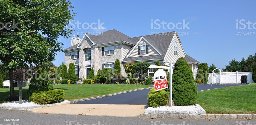 Realtor For Sale Sign on Landscaped Suburban Front Yard stock photo
