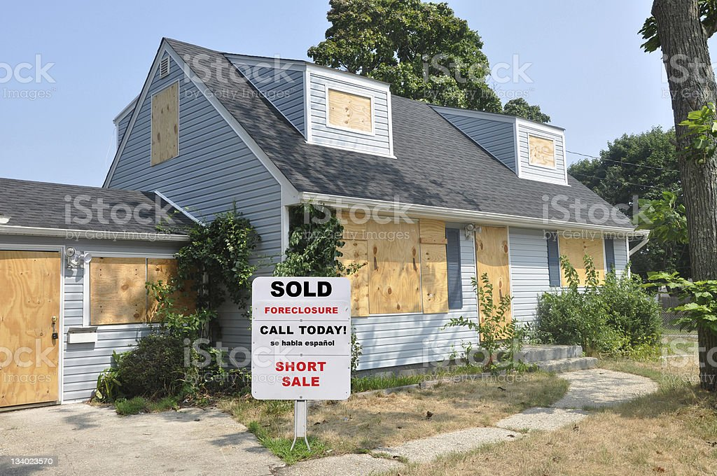 Realtor Foreclosure Sign on Abandoned Cape Code Suburban Home Lawn stock photo