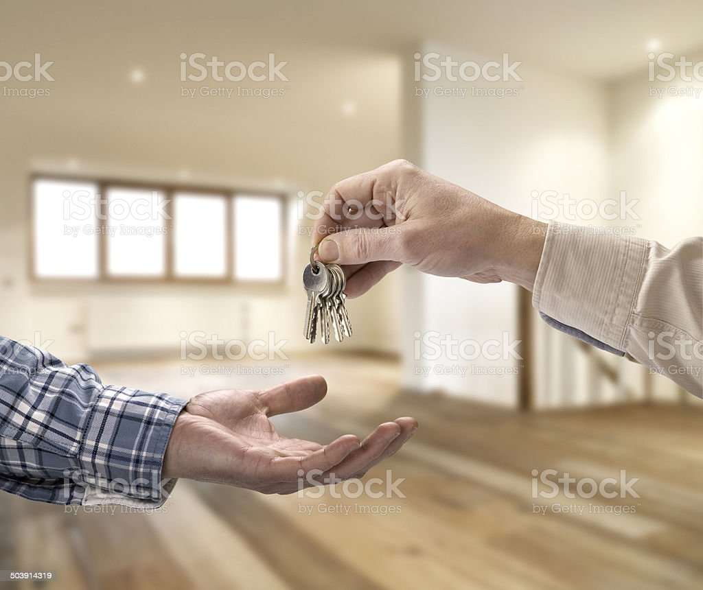 Realtor giving house key to buyer in empty room stock photo