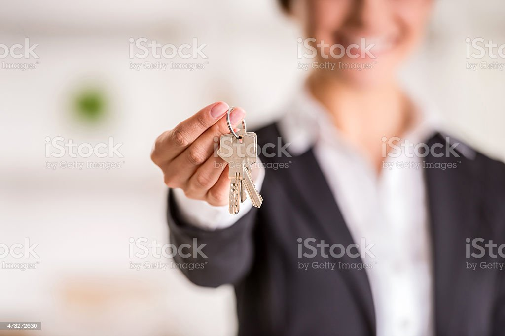 A realtor holding out a set of keys stock photo