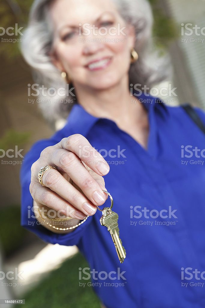 Realtor holding out new house keys royalty-free stock photo