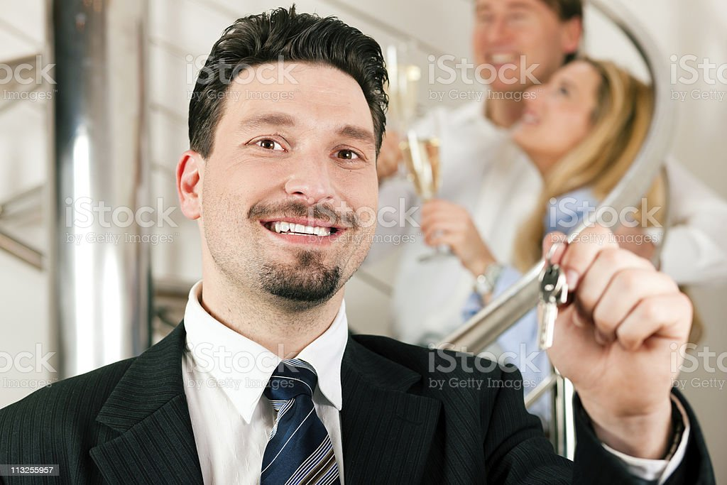 Realtor in apartment giving keys to couple royalty-free stock photo