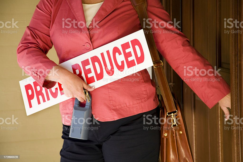Realtor leaving house with Priced Reduced sign royalty-free stock photo