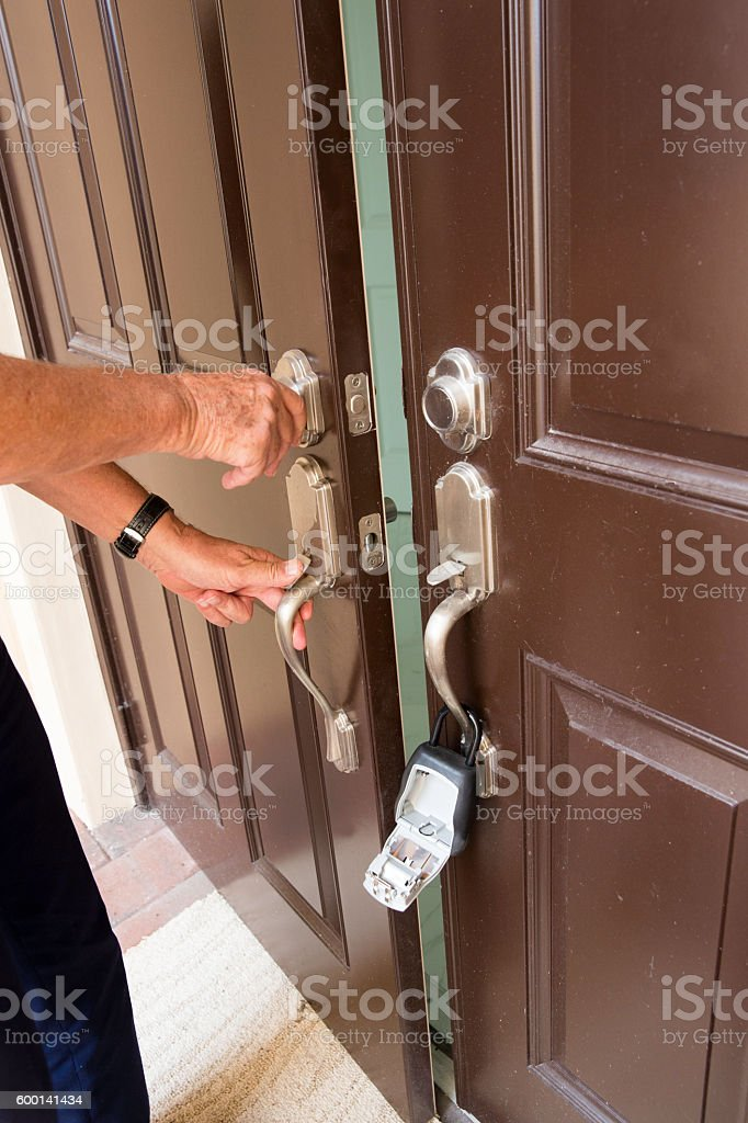Realtor opening home's  door with key from lock box stock photo