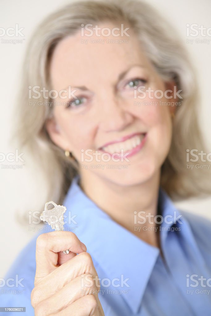 Realtor or Home Owner Holding Out House Key royalty-free stock photo
