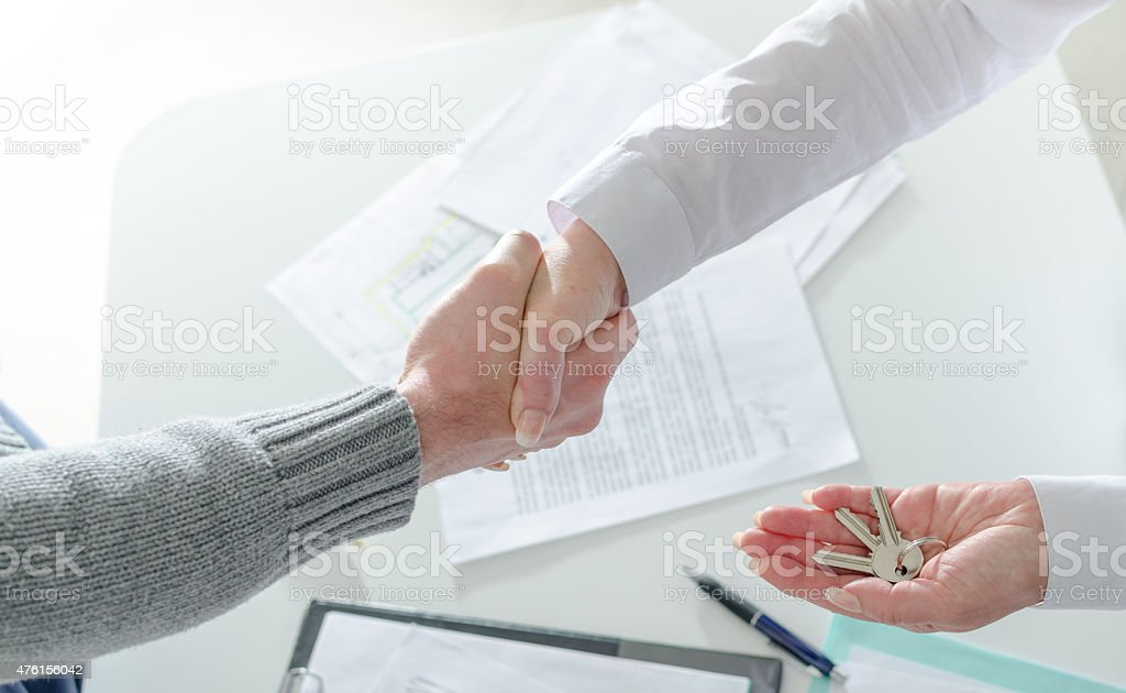 Realtor shaking hands with her client stock photo