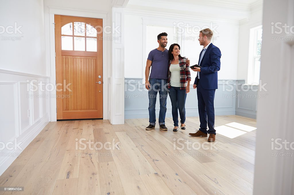 Realtor Showing Hispanic Couple Around New Home stock photo
