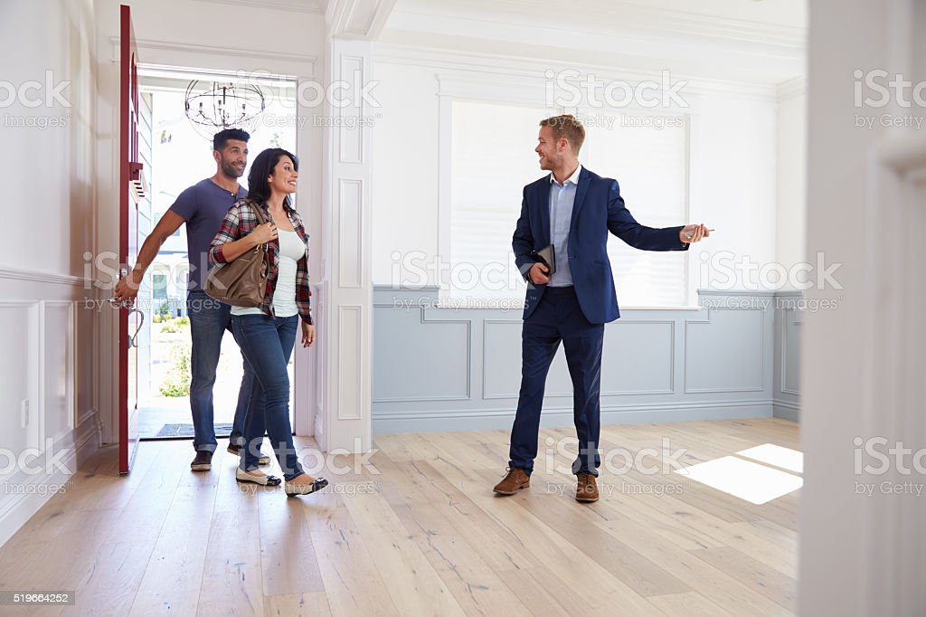 Realtor Showing Hispanic Couple Around New Home stock photo