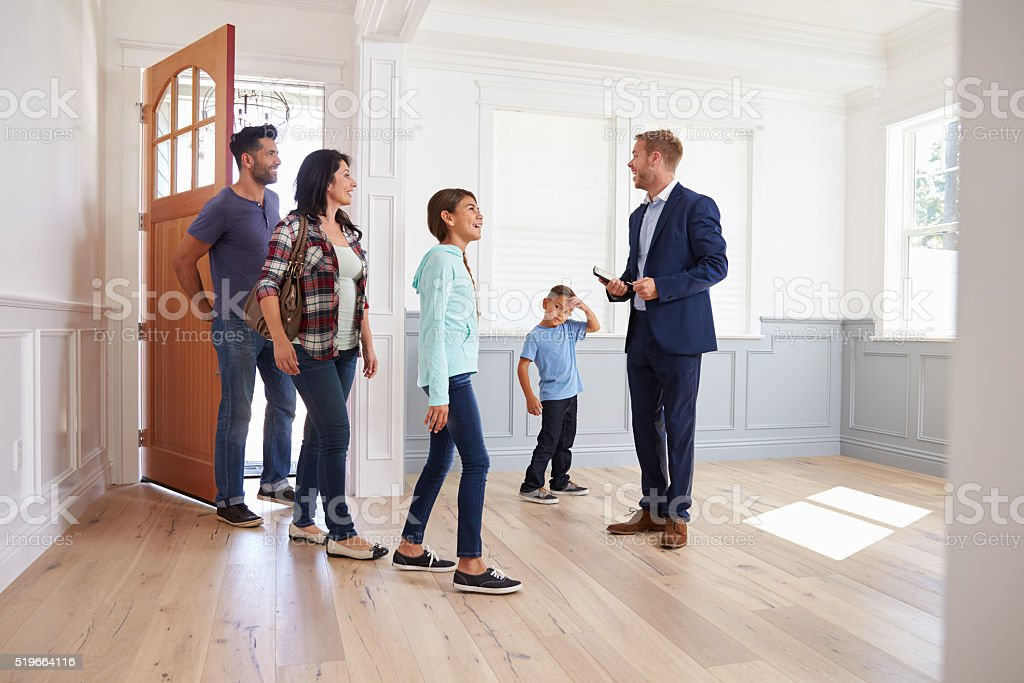 Realtor Showing Hispanic Family Around New Home stock photo