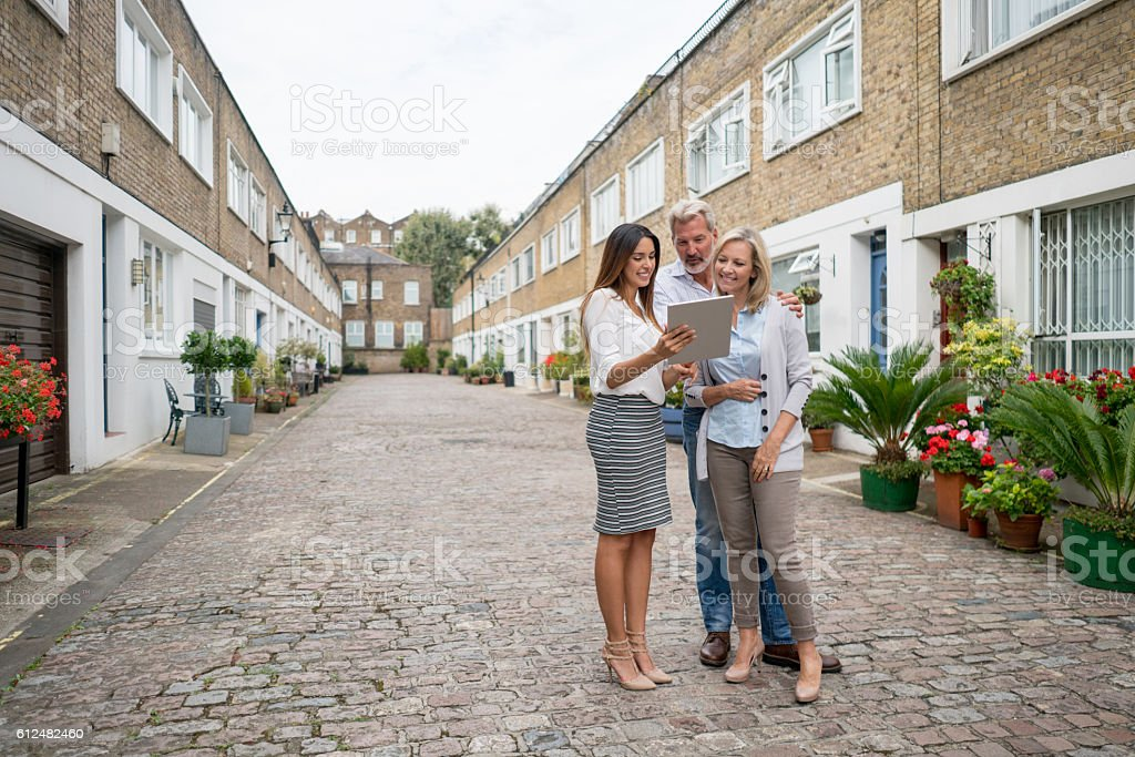 Realtor showing house to a couple stock photo
