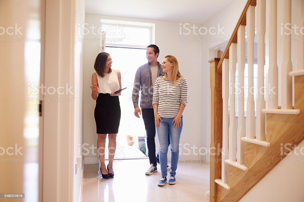 Realtor Showing Young Couple Around Property For Sale stock photo