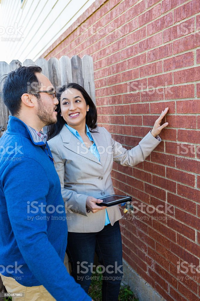 Realtor walks around oustide of house with client stock photo