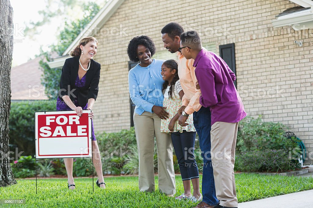 Realtor with black family in front of house for sale stock photo