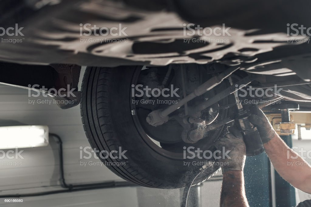 rear car suspension. the garage mechanic raised the car on the lift stock photo