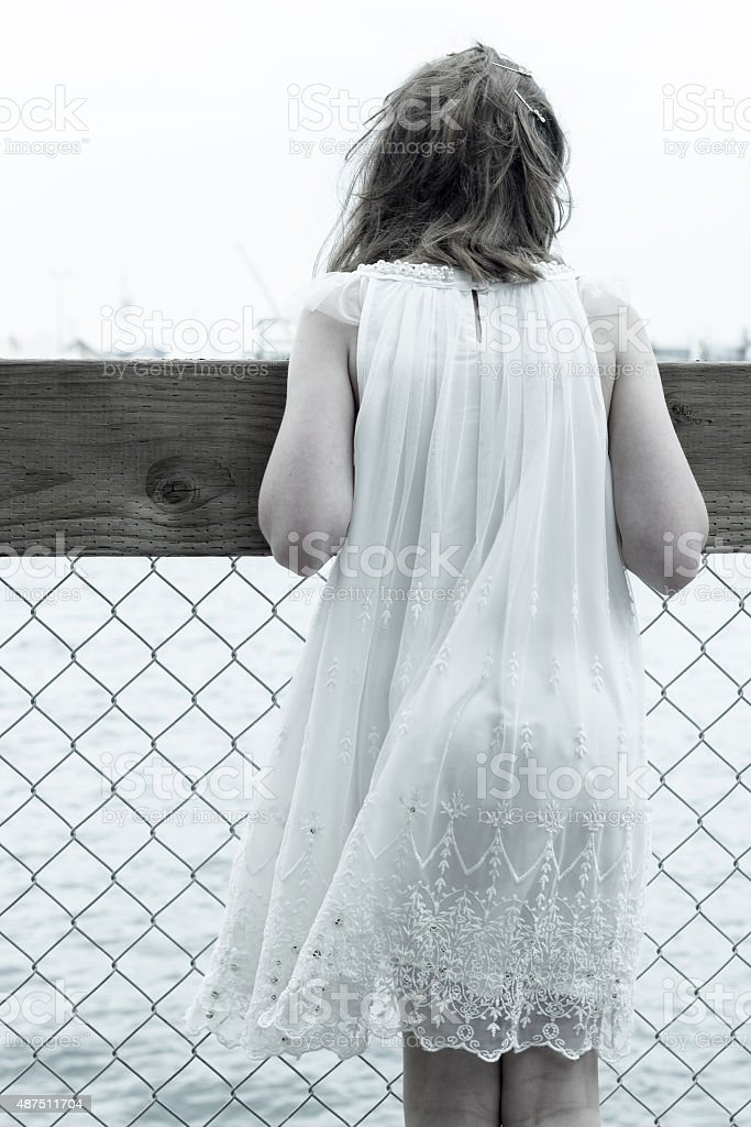 Rear shot of young girl looking out to sea stock photo