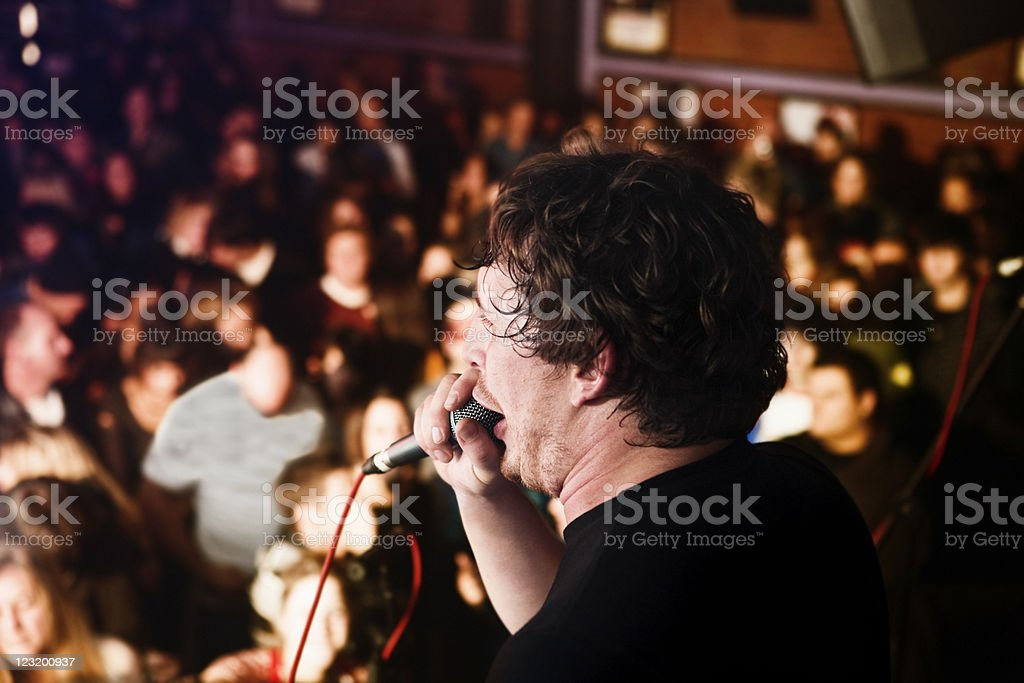 Rear view as young man either sings or speaks passionately stock photo