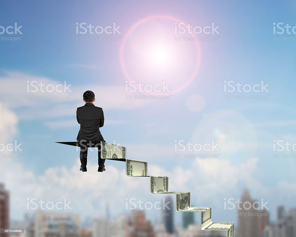 Rear view businessman sitting on top of money stairs stock photo