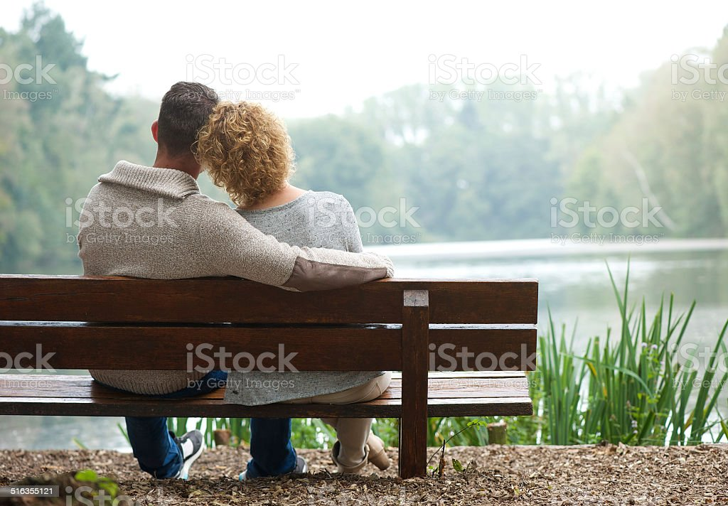 Rear view couple sitting on bench outdoors stock photo