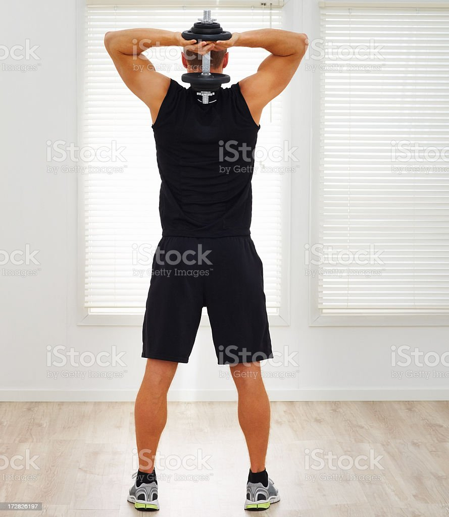 Rear view full length of a young guy exercising his triceps with a dumbbell stock photo